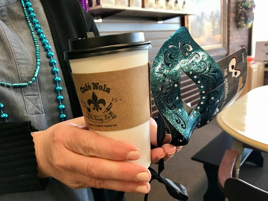 Shannon Carter holds a beverage and a Mardi Gras mask at Cafe Nola's opening day in Kimball Township on Feb. 19, 2020.