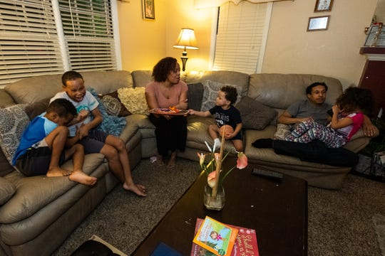 Dalayna McDade-Stepp, center, sits with her family Monday, Feb. 17, 2020, in the living room of their Port Huron home. McDade came to Port Huron with her six children several years ago and credits SONS as a big help for them to get their footing in the city.