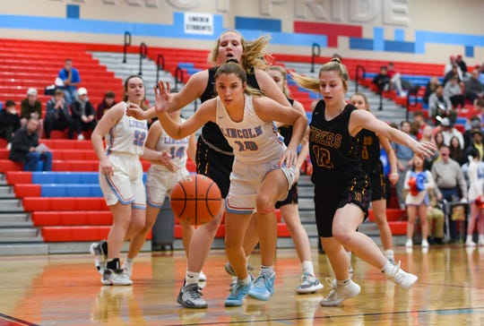 Lincoln's Morgan Hansen and Harrisburg's Emilee Boyer and Carolyn Haar chase after a loose ball on Tuesday, Feb. 18, at Lincoln High School in Sioux Falls.