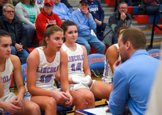 Lincoln's Morgan Hansen and Emma Osmundson listen to head coach Matt Daly during a time out on Tuesday, Feb. 18, at Lincoln High School in Sioux Falls.
