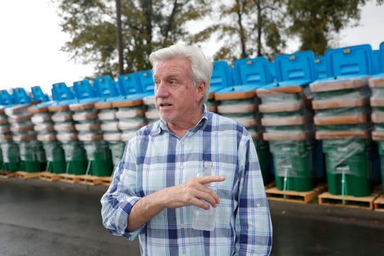Ralph Mills, coastal region vice president for Waste Pro, describes the locking garage cans, which prevents animals from getting into the garbage.