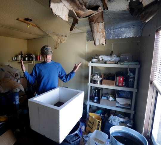 Robert Ihrke, a resident of the Mossy Pond area, 59, shrugs his shoulders as he looks at containers he uses to catch rain water that pours through the hole in his ceiling left by Hurricane Michael in Oct. 2018.