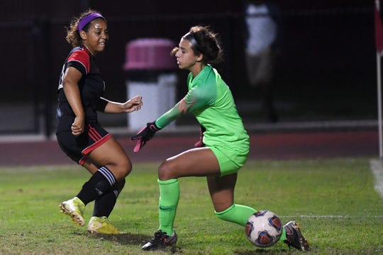 Vero Beach High School's Chayse McGirt puts the ball by Boca Raton goalkeeper Lara Larco on Tuesday, Feb. 18, 2020, during the Region 3-7A championship game at the Citrus Bowl in Vero Beach. McGirt's goal was the only goal of the game as the Lady Indians beat Boca Raton 1-0 to advance to the state semifinal.