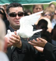09/04/2009 David Marmolejo watched the release of a dove held by brother Manny Marmolejo in memory of their mother, Gloria Marmolejo, during a graveside service at Evergreen East Cemetery.