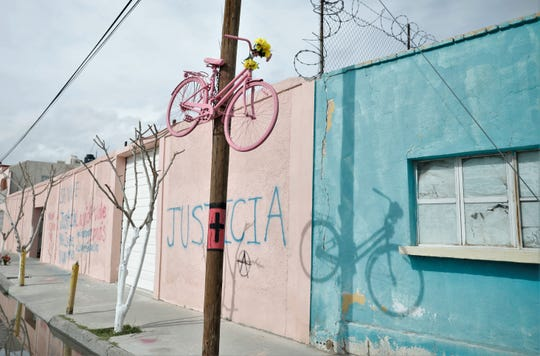 A pink spray painted bike is pinned to a telephone poll near where Isabel Cabanillas was found murdered.