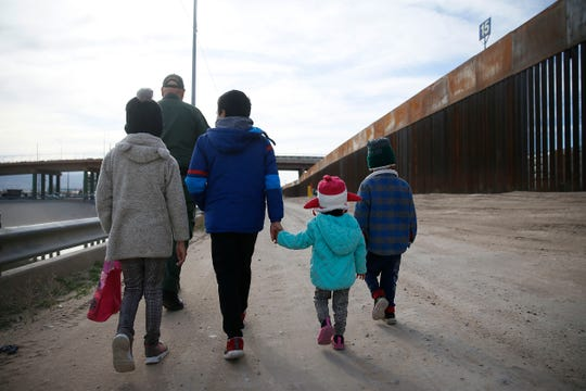 Border patrol agent Joe Romero escorts four unattended migrant children from Ecuador to another agent for transport on Feb. 18, 2020 near the Stanton Street Bridge. The children told agent Romero they did not have parents with them. They were apprehended before the Trump administration instituted new protocol to expel minors during the coronavirus pandemic.