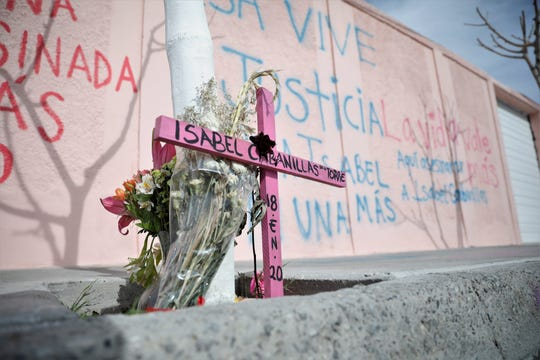 A pink cross with Isabel Cabanillas' name on it is left near where she was found murdered.