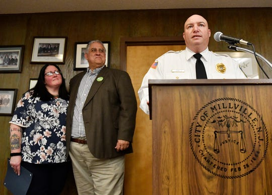 Recently retired Millville Police Officer Sue Taylor and Commissioner Joseph Pepitone listen to Chief Jody Farabella (podium) during a presentation at the City Commission meeting on Tuesday, Feb. 19, 2020.