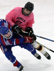 From left, Carmel's Gavin Golisano (15) and Cortlandt's P.J. Kowal (44) get tangled up while going after the puck during hockey action at the Brewster Ice Arena in Brewster Feb. 7, 2020. The teams played t a 3-3 tie.