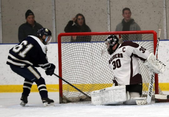 From left, Rye Country Day School's Jake Oddi (61) gets a shot by Scarsdale goalie Max Kushnick (30) for a second period goal during hockey action at Rye Country Day School  Feb. 19, 2020. RCDS won the game 4-1.