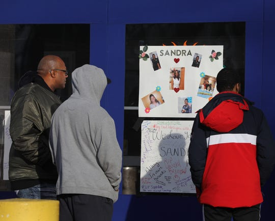 Ronnie Wilson, left, along with other family members look at a memorial for his slain sister Sandra Wilson before attending a press conference at Finkelstein Library in Spring Valley Feb. 19, 2020.