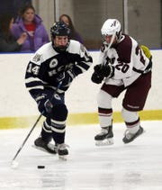 From left,  Rye Country Day School's George Megdanis (14) in front of Scarsdale Kyle Kahan (20) during hockey action at Rye Country Day School  Feb. 19, 2020. RCDS won the game 4-1.