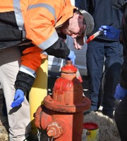 Terence Woollis of Work Services Corporation paints a fire hydrant on the property Wednesday following an announcement that WSC would take over the task of painting the city's 2,800 hydrants for the Wichita Falls Fire Department.