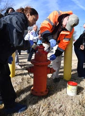 Paymshia Duval and Terence Woollis of Work Services Corporation paint a fire hydrant Wednesday morning. WSC is partnering with the Wichita Falls Fire Department to paint the 2,800 fire hydrants in the city.