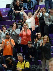 New Lexington fans celebrate the team's 53-43 win against Sheridan in a Division II sectional on Tuesday at Logan High School.
