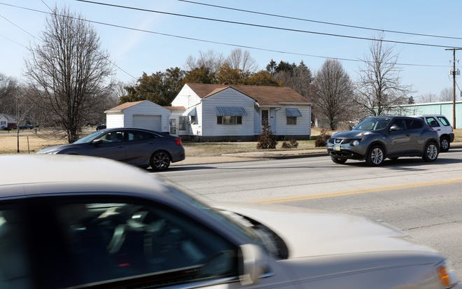 Traffic streams past the site of a proposed development on Maple Avenue just north of County Club Drive in Zanesville.  Rezoning for the four plots in question was on hold by the Zanesville Planning Commission.