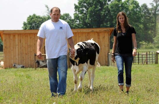 Ryan Newman and Krissie Newman walk with a cow at their Rescue Ranch for animals in 2014.
