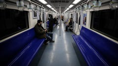 FILE - In this Feb. 17, 2020, file photo, commuters ride in a quiet subway train during the morning rush hour in Beijing