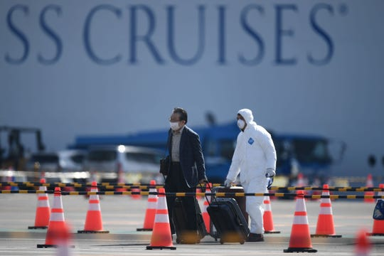 A passenger (L) disembarks from the Diamond Princess cruise ship - in quarantine due to fears of the new COVID-19 coronavirus - at the Daikoku Pier Cruise Terminal in Yokohama on February 19, 2020.