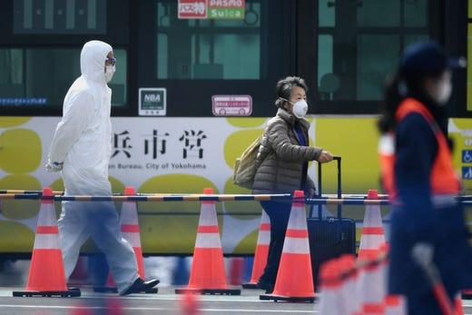 2020年2月19日,在游轮的冠状病毒检疫工作结束后,一名乘客在日本横滨Daikoku码头游轮码头从钻石公主号游轮下船后离开。