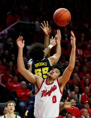 Feb 19, 2020; Piscataway, New Jersey, USA; Michigan Wolverines guard Eli Brooks (55) and Rutgers Scarlet Knights guard Geo Baker (0) battle for the ball during the first half at Rutgers Athletic Center (RAC).