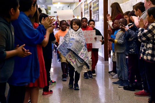 David Webster, a third-grade student at Lee Elementary School, is cheered by the student body as he walks through the halls with his classmates Thursday. David is leaving school for the rest of the current school year to undergo a bone marrow transplant.