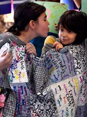 David Webster, 9, pulls back as his sister, Rose, purses her lips for a kiss during a group photo at Lee Elementary School.