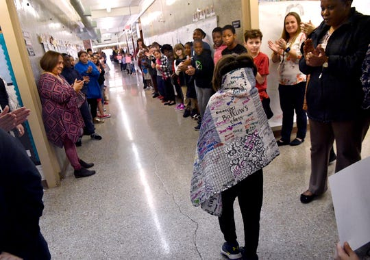 Lee Elementary School students and staff line the hallway to cheer David Webster on Thursday.