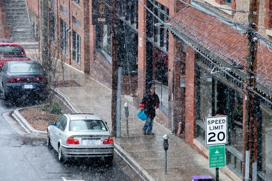 A man spreads salt on the sidewalk as wet snow falls on downtown Asheville on Feb. 20, 2020.