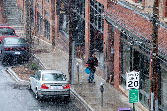 A man spreads salt on the sidewalk as wet snow falls on downtown Asheville on Feb. 20, 2020.