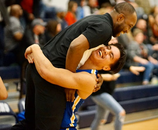 Bremerton's Kelo Legova lifts Knights head coach Miah Davis after the team's 54-52 win over Steilacoom on Wednesday in the Class 2A West Central District boys basketball tournament.