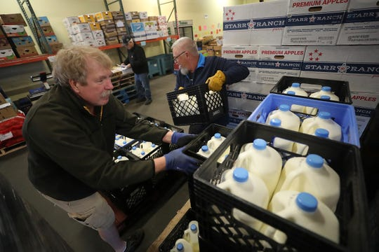 Volunteers Syd Brown, of Silverdale, left, and Paul Wright, of Bremerton, stack crates of milk on a pallet headed for South Kitsap after delivery to the Bremerton Foodline on Thursday. A tariff war with China has resulted in an increase of federal commodities on food bank shelves.