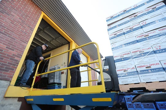 Mike Peterson, left, mans the ramp controls as fellow volunteer Paul Wright carefully wheels boxes of apples off of the delivery truck at Bremerton Foodline on Thursday.