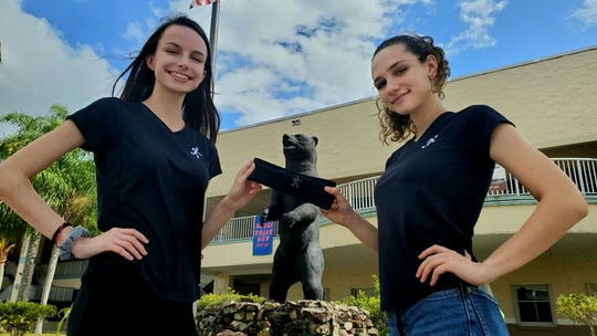 """Bayside High juniors Aubrey Harasen and Madison Bohlin model their """"Fearless Band,"""" a high-tech headband that measures the user's body temperature and alerts when they are in danger of heatstroke."""