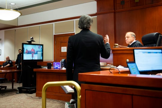 Judge Mark P. Tarantino, right, speaks with defense attorney Richard A. Isolda as Andrew Mack, 31, is seen via video for a first appearance at Burlington County Superior Court in Mount Holly, N.J. Thursday, Feb. 20, 2020. Mack is the father of a 4-year-old who accidentally shot and killed himself.