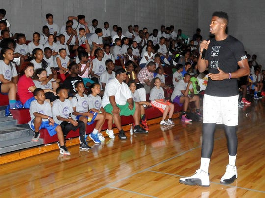 Jason Thompson talks to a group of kids during a basketball camp in 2015.
