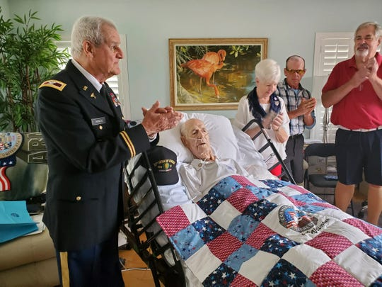Cornerstone Hospice veteran volunteer Ret. Col. Paul Farineau honored veteran George Yankowski with a quilt made by a Chillicothe native as Yankowski's wife, Mary applauds.