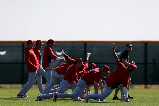 Cincinnati Reds minor-league players stretch before the major-league players take the field, Thursday, Feb. 20, 2020, at the baseball team's spring training facility in Goodyear, Ariz.