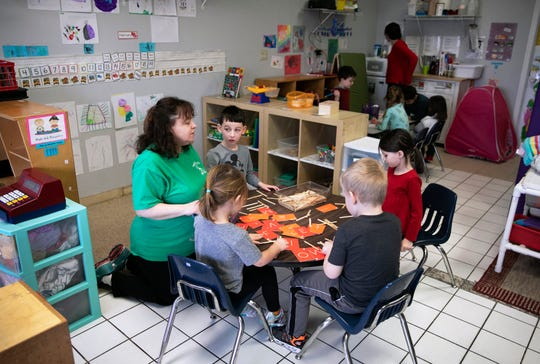 Kathy Donelan works with children at her Northern Kentucky child care center, Aunt Kathy's Child Care and Preschool, in this file photo taken before the new coronavirus led to a statewide shutdown of such facilities.