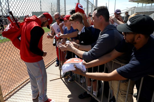 Cincinnati Reds second baseman Mike Moustakas (9) signs autographs for fans at the conclusion of spring practice, Thursday, Feb. 20, 2020, at the baseball team's spring training facility in Goodyear, Ariz.