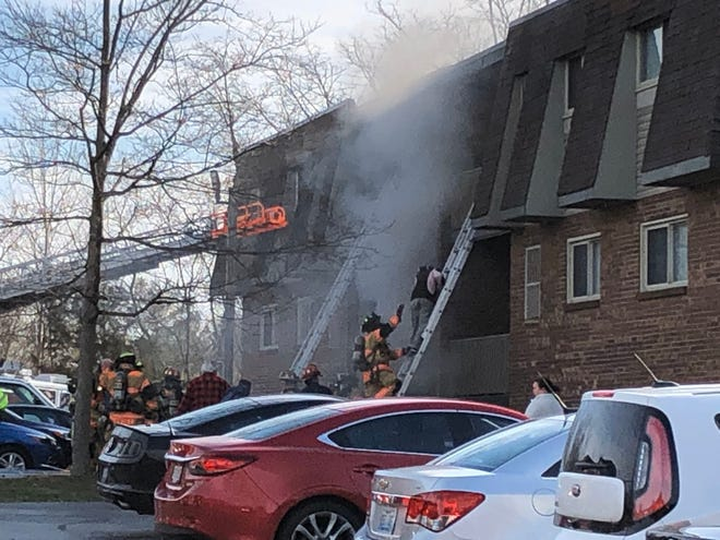 Firefighters work to rescue people from an apartment building Thursday in the 600-block of Commons Drive in Miami Township.