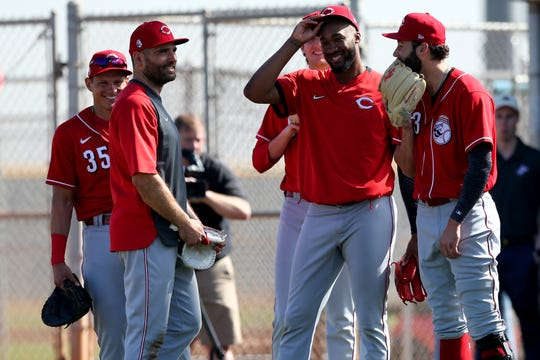Cincinnati Reds first baseman Joey Votto (19) jokes with pitchers Amir Garrett (50) and Cody Reed (23), Wednesday, Feb. 19, 2020, at the baseball team's spring training facility in Goodyear, Ariz.