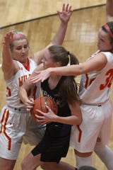 Carlisle seniors Kennedy Preston and Molly Hoekstra try to trap Norwalk junior Bren Moritz. Carlisle edged Norwalk 34-40 in the first round of the Class 4A playoffs Feb. 19, 2020 in Carlisle.