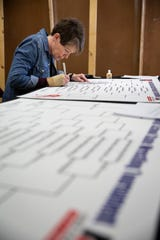 Calligrapher Tammie Ollendick of Grimes works on writing the names of wrestlers on the brackets on Thursday, Feb. 20, 2020, in Des Moines. Ollendick has been the Associations Calligrapher since 1989 but for the past three years her daughter Zoe has done it. Training with the National Guard took Zoe away this year but Tammie said she got right back into the groove.