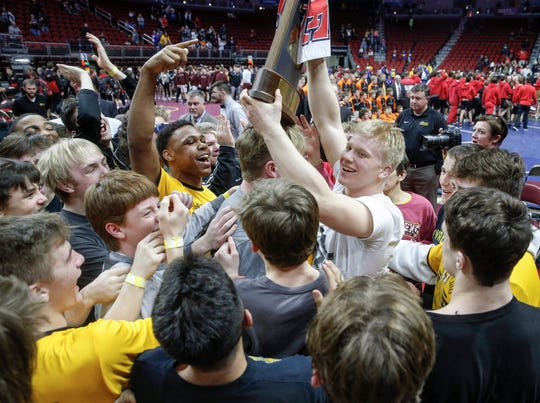 Members of the Southeast Polk Rams wrestling team celebrate a Class 3A team trophy after a win over Waverly-Shell Rock during the 2020 Iowa high school wrestling dual state tournament at Wells Fargo Arena in Des Moines on Wednesday, Feb. 19, 2020.