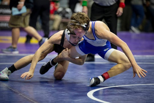 Aybren Moore of Atlantic, black, wrestles Rylie Anderson of Bondurant-Farrar, blue, during their first round 2A match at Wells Fargo Arena on Thursday, Feb. 20, 2020, in Des Moines. Anderson would go on to win by a 6-3 decision.