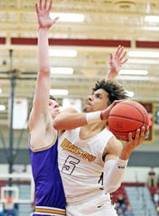 Ankeny senior Braxton Bayless (5) shoots around the tough defense of Johnston junior Max Roquet (44) as the Johnston Dragons compete against the Ankeny Hawks in high school boys' basketball on Friday, February 14, 2020 at Ankeny High School. The Jaguars won 70 to 55.