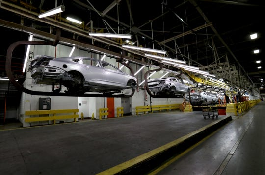 A 2020 Chevrolet Impala still to be painted is moved on a hoist on the production line on Thursday at the GM Detroit-Hamtramck Assembly plant.
