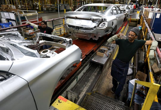Gregory Edwards, 64, of Detroit takes pictures of the very last 2020 Chevrolet Impala that was making its way down the production line on Thursday inside Detroit-Hamtramck Assembly.
