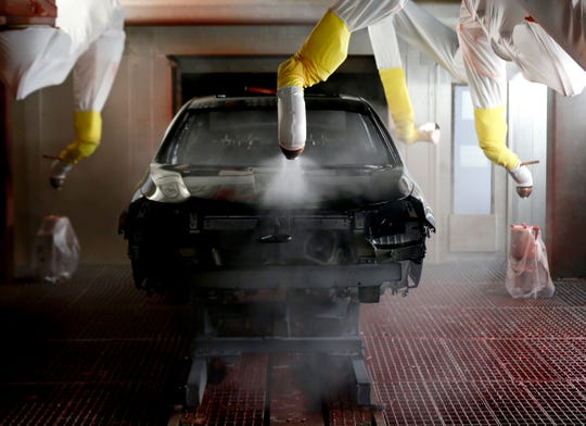 A recently painted black 2020 Chevrolet Impala gets a clear coat applied to it by robots in the paint shop on Thursday at GM's Detroit-Hamtramck Assembly.